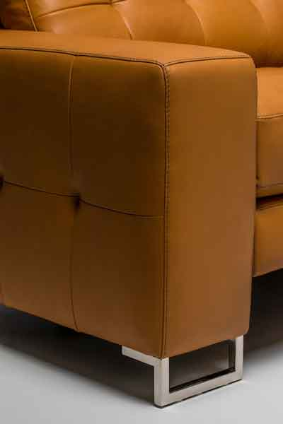 Close-up detail of Hudson arm, chrome foot and tufting detail. High-style motion furniture.
