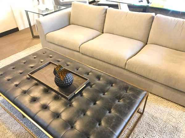 Neutral modern sofa with leather ottoman by Design Des Moines