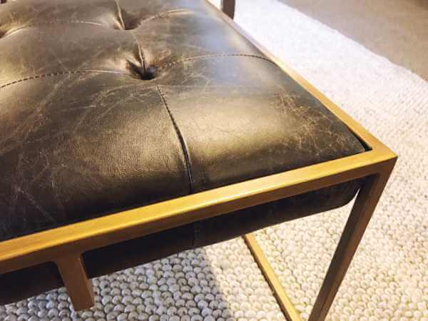 Gold frame on a black leather ottoman by Design Des Moines