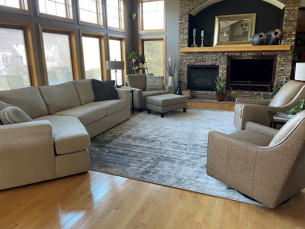 After design image of living room space with large windows and fire place. Milford two piece sectional with cuddle chaise and Louise Cuddle Chair and ottoman on left side of image. Stephanie swivel gliders in leather on right side of image. Rug pulls the whole room together.